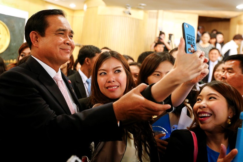 Thailand's Prime Minister Prayuth Chan-ocha poses for a 'selfie' picture with a stock exchange officer at the Stock Exchange of Thailand in Bangkok February 26, 2015. Photo: Reuters