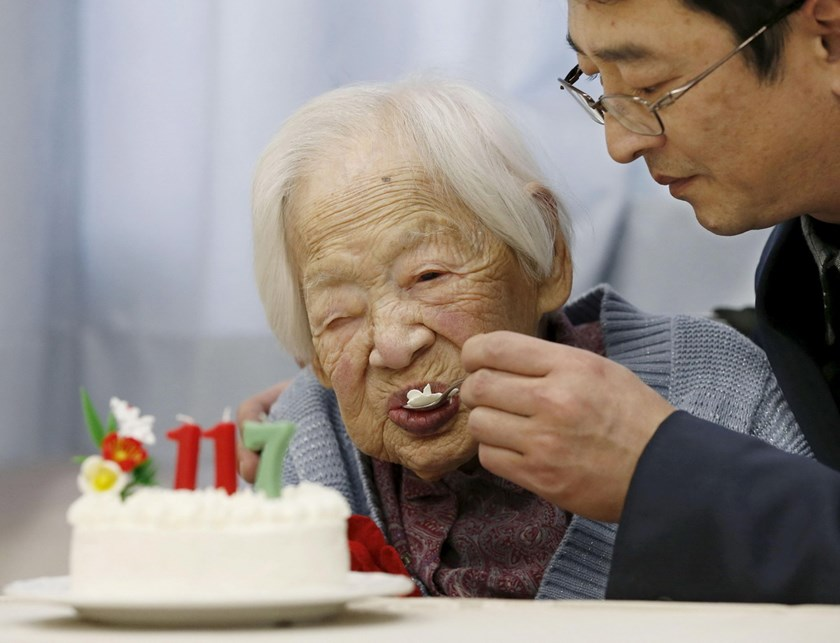 Japanese Misao Okawa, the world's oldest living person, is assisted while eating her birthday cake as she celebrates her 117th birthday at an elder care facility in Osaka, western Japan in this file photo taken by Kyodo March 5, 2015. Photo: Reuters/Kyodo