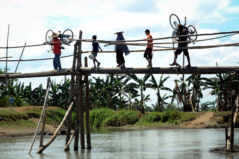Filipinos cross a makeshift foot bridge in Mamasapano, Maguindanao in southern Philippines March 31, 2015. Photo: Reuters