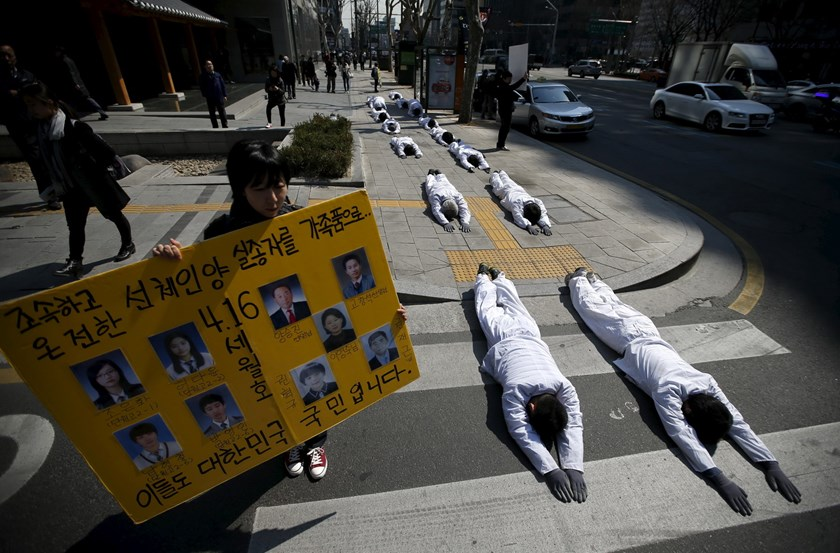 "A woman holds a banner bearing portraits of victims of sunken ferry Sewol next to Buddhist believers performing during a ""three steps one bow"" ceremony to urge the government to salvage the sunken ferry Sewol as soon as possible, in central Seoul March 26"
