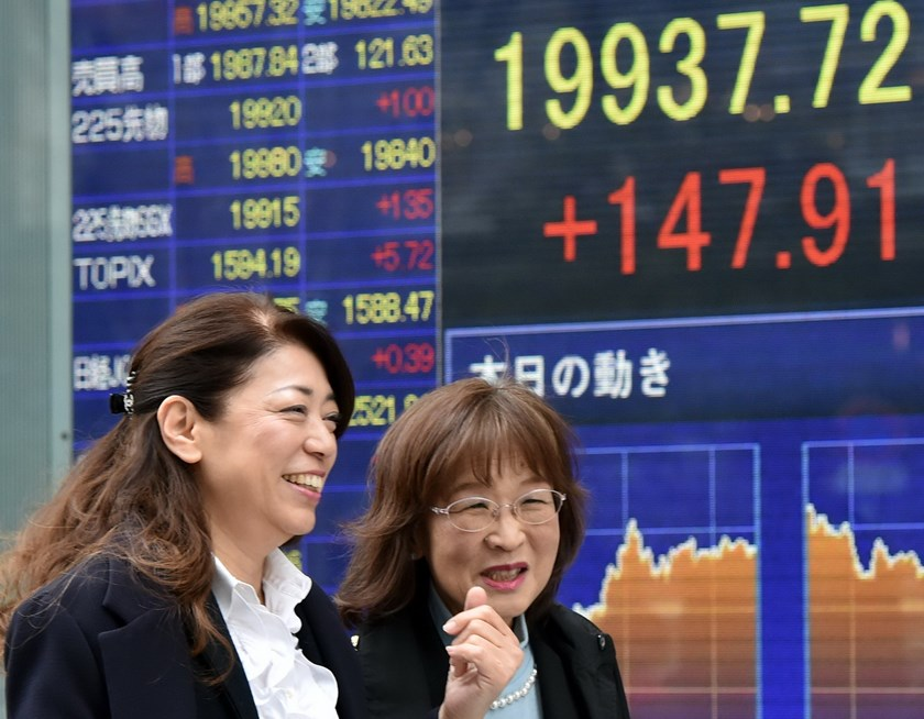 Pedestrians walk past a share prices board in Tokyo on April 9, 2015. Photo: AFP