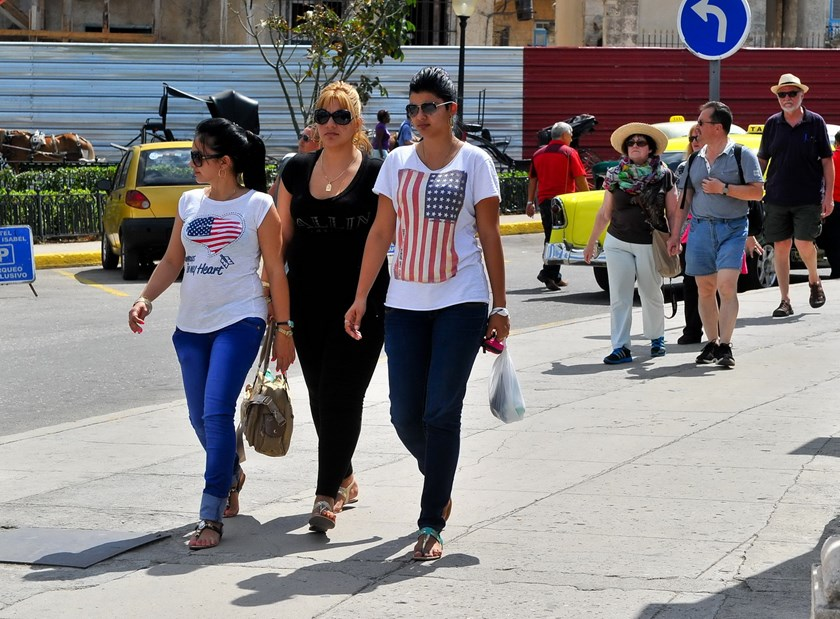 Two women wearing t-shirts with the US flag walks along a street of Havana, on April 13, 2015. Photo: AFP