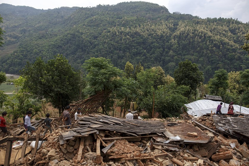 Villagers walk past a damaged house where three were killed by the earthquake at Jharibar Village, in Gorkha, Nepal April 28, 2015. Photo: Reuters