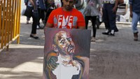 Chintu Sukumaran, brother of Australian death row prisoner Myuran Sukumaran, carries a self-portrait painted by Myuran Sukumaran at Wijayapura port in Cilacap, Central Java, Indonesia, April 28, 2015. Photo: Reuters/Beawiharta