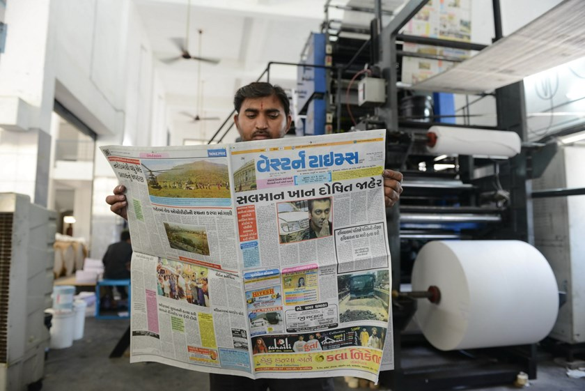 "An Indian supervisor goes through a printed copy of the Gujarati-language 'Western Times' which features the news of Indian Bollywood actor Salman Khan, ""Salman Khan Convicted"" with the actor's photo, in the village of Shilaj, some 20 kms from Ahmedabad o"