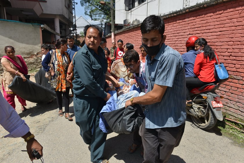 Nepalese patients are carried out of a hospital building as a 7.4 magnitude earthquake hits the country, in Kathmandu on May 12, 2015. Photo: AFP/Prakash Mathema