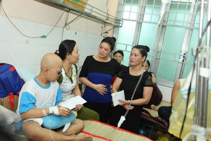 Nguyen Kim Anh (1st, R), a founder of THANH KOCH restaurants in Berlin, and Do Thi Kim Lien, Honorary Consul of South Africa in Ho Chi Minh City, talk with the mother of a child patient at the HCMC Oncology Hospital on May 15, 2015. Photo supplied
