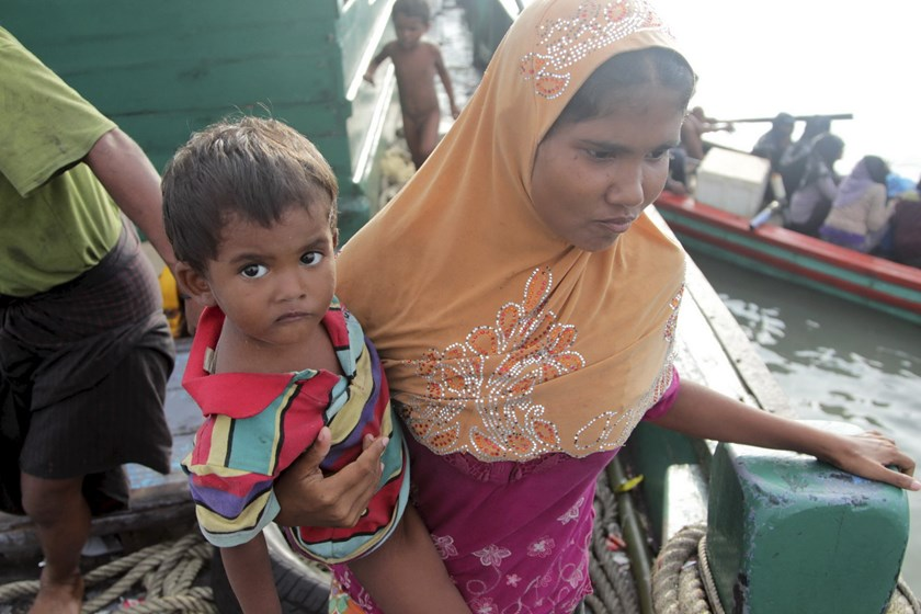 A Rohingya migrant carrying a child stands onboard a fishing boat before being transported to shore, off the coast of Julok, in Aceh province, May 20, 2015 in this photo taken by Antara Foto. Photo: Reuters/Syifa/Antara Foto