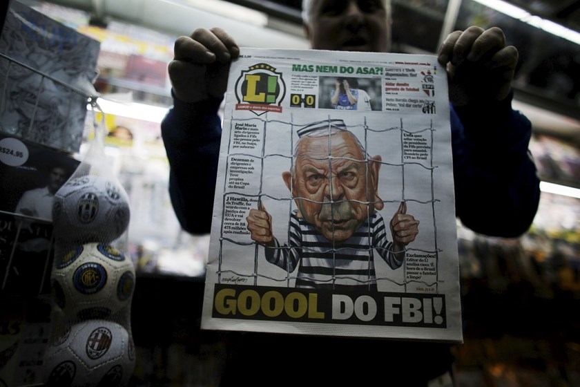 "A man shows a Brazilian newspaper front page with a caricature of former President of the Brazilian Football Confederation (CBF), Jose Maria Marin, with a headline reading ""Goal of the FBI"", in Sao Paulo May 28, 2015. Photo: Reuters/Nacho Doce"