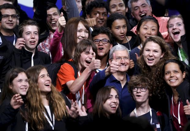 Apple CEO Tim Cook poses with scholarship winners following his keynote address at the Worldwide Developers Conference in San Francisco, California June 8, 2015. Photo: Reuters/Robert Galbraith