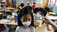 An elementary school student wearing a mask to prevent contracting Middle East Respiratory Syndrome (MERS), receives a temperature check at an elementary school in Seoul, South Korea, June 9, 2015. Photo: Reuters/Kim Hong-Ji