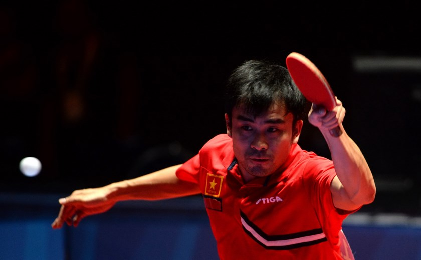 Tran Tuan Quynh of Vietnam plays a shot during the men's team table tennis final match against Li Hu of Singapore at the 28th Southeast Asian Games (SEA Games) in Singapore on June 8, 2015. Photo: AFP/Sajjad Hussain
