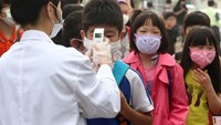 A health worker (L) checks the body heat of children wearing face masks at an elementary school in Pyeongtaek, 65 kms south of Seoul, on June 15, 2015 as the school is reopened after a temporary closure in response to public fears over Middle East Respiratory Syndrome (MERS). Photo: AFP/Yonhap