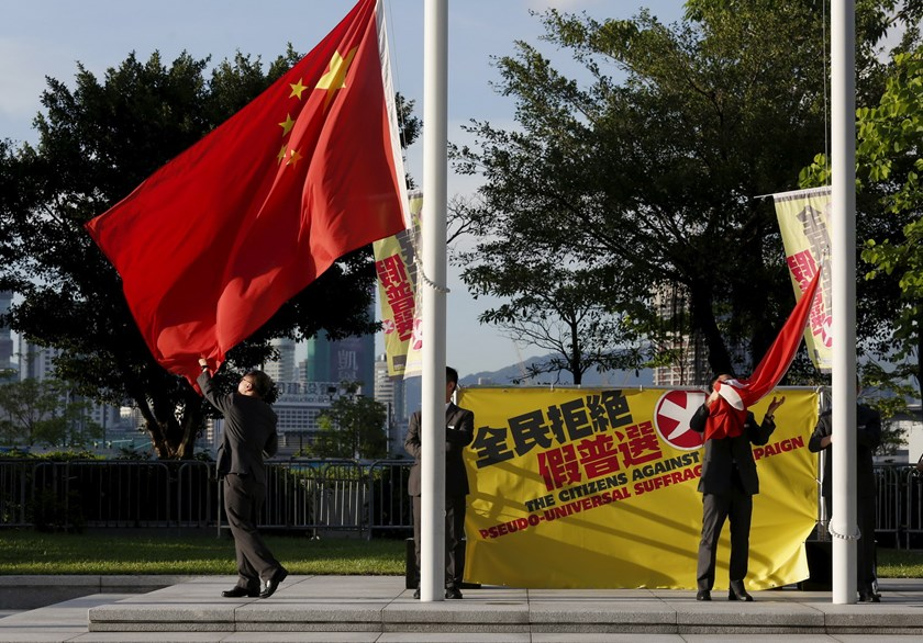 Flagbearers lower a Chinese national flag (L) and a Hong Kong flag beside a banner set up by pro-democracy protesters outside Legislative Council in Hong Kong, China June 16, 2015. Photo: Reuters/Bobby Yip