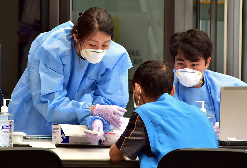 South Korean medical workers wearing face masks check a visitor at a special clinic where patients with respiratory issues can be treated in an isolated space to prevent possible spread to other patients, at Severance Hospital in Seoul on June 16, 2015. Photo: AFP/Jung Yeon-Je