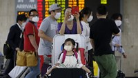 A girl wearing a mask to prevent contracting Middle East Respiratory Syndrome (MERS) sits on a luggage as others walk past them at Gimpo International Airport in Seoul, South Korea, June 17, 2015. Photo: Reuters/Kim Hong-Ji