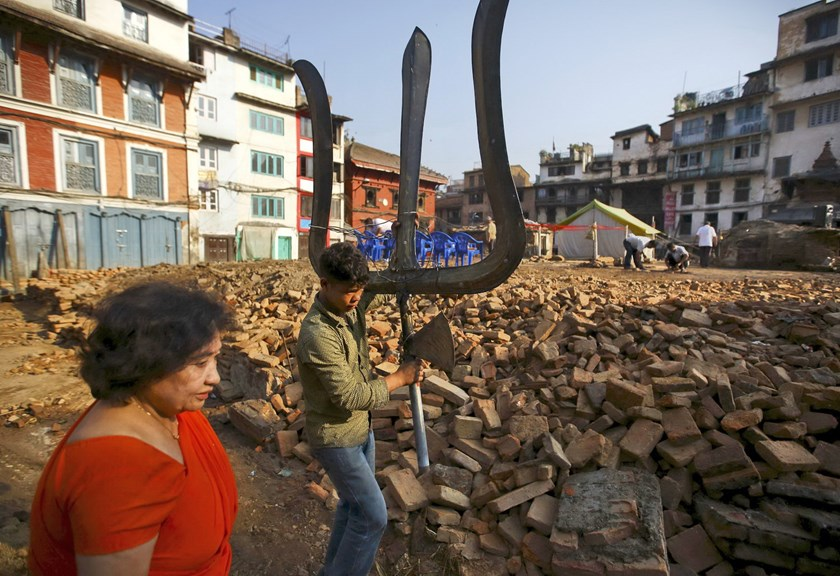 "A photo taken June 8, 2015 shows a boy walking along the debris of a collapsed temple carrying a trident, which is locally called ""Trishul"", a weapon used by Lord Shiva also known as the god of destruction, after the April 25 earthquake in Kathmandu, Nepal . Photo: Reuters/Navesh Chitrakar"