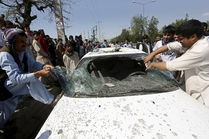 Afghan men remove the broken window of a car at the site of a suicide bomb attack in Kabul, Afghanistan, June 30, 2015. Photo: Reuters/Omar Sobhani