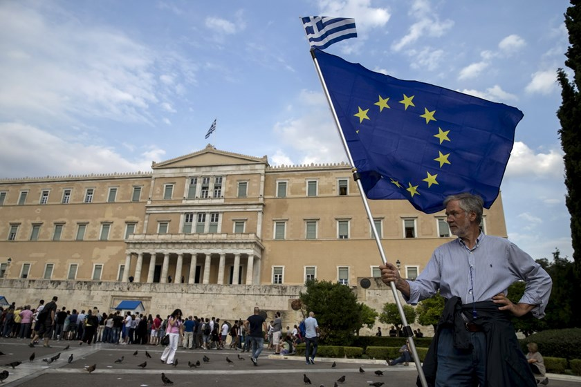 A pro-Euro protestor holds a European Union flag with a Greek national flag on top during a rally in front of the parliament building in Athens, Greece, June 30, 2015. Photo: Reuters/Marko Djurica