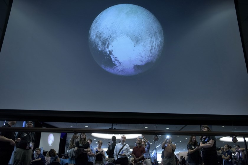 People look at an early image of Pluto taken by NASA's New Horizons probe as the craft makes its closest fly-by of the dwarf planet at the Johns Hopkins University Applied Physics Laboratory July 14, 2015 in Laurel, Maryland. Photo: AFP/Brendan Smialowski
