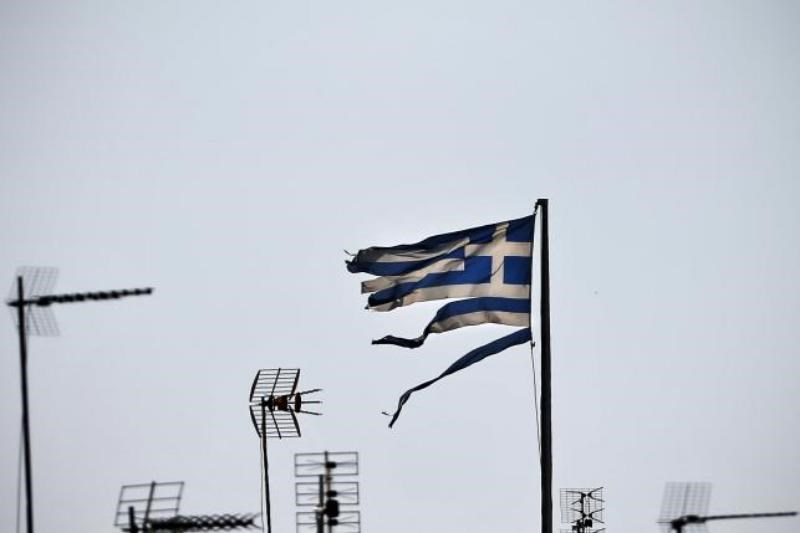 A frayed Greek national flag flutters among antennas atop a building in central Athens, Greece July 20, 2015. Photo: Reuters/Alkis Konstantinidis