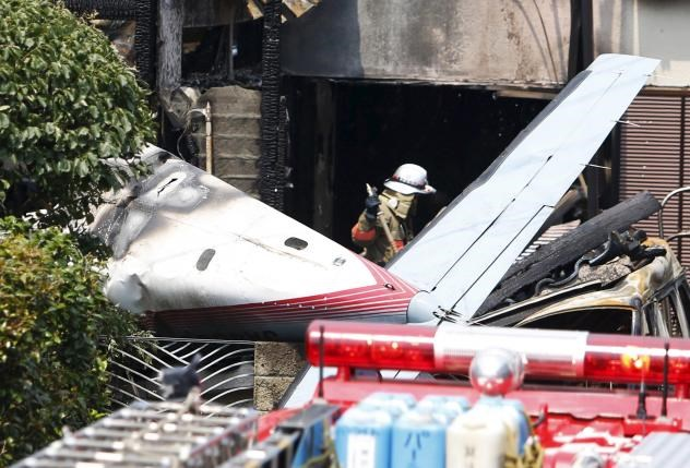 The tail section of a crashed light plane and burning house are seen after the plane went down in a residential area and burst into flames, in Chofu, outskirt of Tokyo, July 26, 2015. Photo:Reuters/Yuya Shino