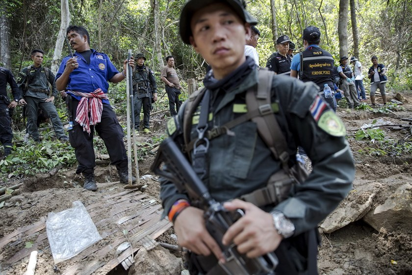 Security forces and rescue workers watch as human remains are retrieved from a mass grave at an abandoned camp in a jungle some three hundred meters from the border with Malaysia, in Thailand's southern Songkhla province in this May 2, 2015 file photo. Photo: Reuters/Damir Sagolj/Files