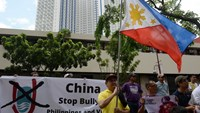 Anti-China protesters display the national flag during a protest in front of the Chinese consulate in the financial district of Manila on July 24, 2015. Photo: AFP/Ted Aljibe