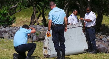 French gendarmes and police inspect a large piece of plane debris which was found on the beach in Saint-Andre, on the French Indian Ocean island of La Reunion, July 29, 2015. Photo: Reuters/Zinfos974/Prisca Bigot