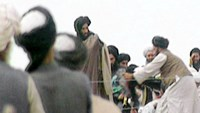 A file picture taken in Kandahar on an undisclosed date in 1996 shows a TV screengrab of footage taken secretly by BBC Newsnight which claims to show the Afghan Taliban's one-eyed leader Mullah Mohammed Omar (C) during a rally for his troops in Kandahar, before their victorious assault on Kabul. The Afghan government is investigating reports of the death of Taliban supremo Mullah Omar, a presidential spokesman said July 29, 2015, amid frenzied speculation about the rumoured demise of the reclusi