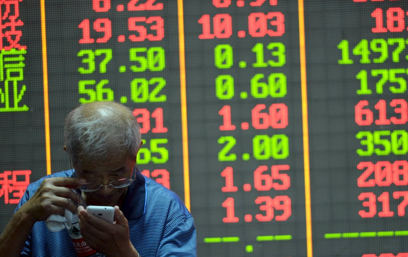 An investor checks on his mobile phone in front of an electronic board showing stock information at a brokerage house in Hangzhou, Zhejiang province, China, July 29, 2015. Photo: Reuters/Stringer