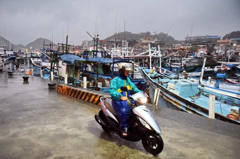 A man rides past fishing boats moored in a shelter at Nanfangao harbor in Yilan on August 6, 2015 as typhoon Soudelor approaches eastern Taiwan. Photo: AFP/Sam Yeh
