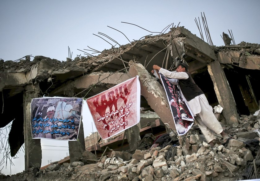 An Afghan civil society member hangs a banner on a destroyed building at the site of a truck bomb blast in Kabul, Afghanistan August 8, 2015. Photo: Reuters/Ahmad Masood