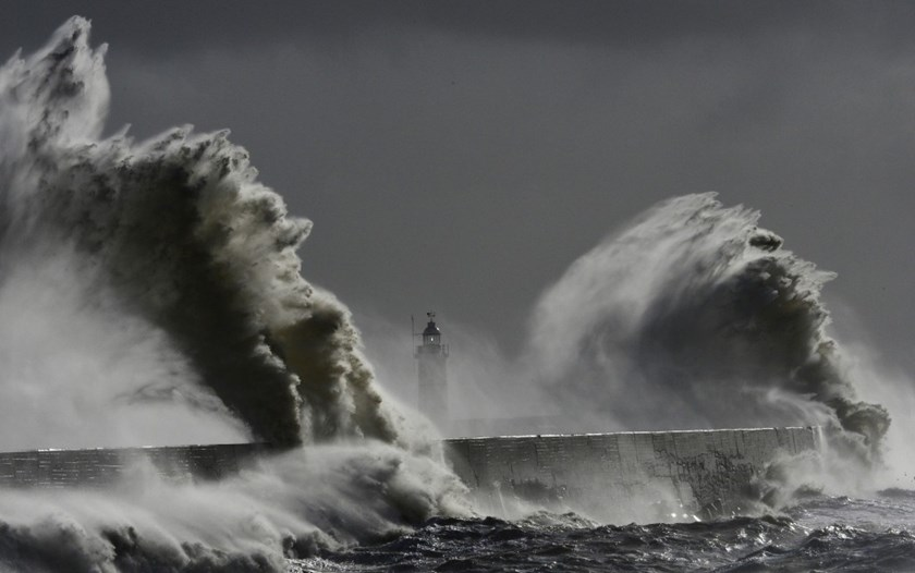 Large waves hit the lighthouse and harbor at high tide at Newhaven in Sussex, southern England, February 15, 2014. Photo: Reuters/Toby Melville