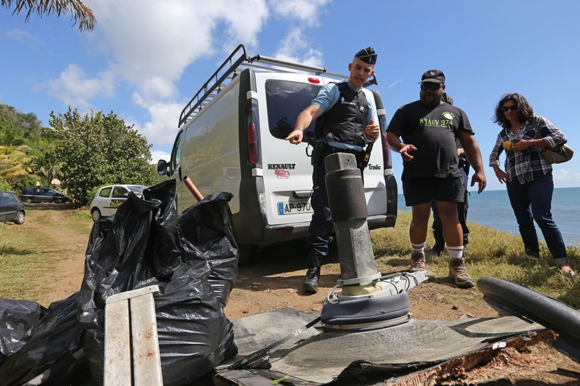 A French Gendarme (L) points at debris found by local ecological associations and volunteers on August 11, 2015 in the eastern part of Sainte-Suzanne, on France's Reunion Island in the Indian Ocean, during search operations for the missing MH370 flight conducted by French army forces and local associations. Photo: AFP/Richard Bouhet