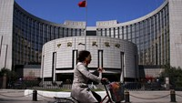 A woman rides past the headquarters of the People's Bank of China, the Chinese central bank, in Beijing, in this April 3, 2014 file photo. Photo: Reuters/Petar Kujundzic/Files