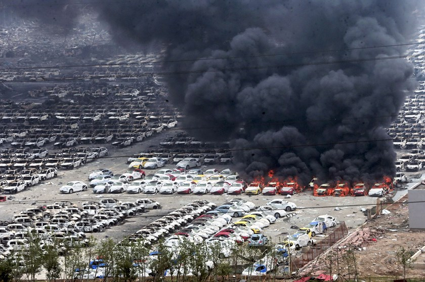 Smoke rises as damaged vehicles are seen burning near the site of Wednesday night's explosions, at Binhai new district in Tianjin, China, August 15, 2015. Photo: Reuters/Stringer