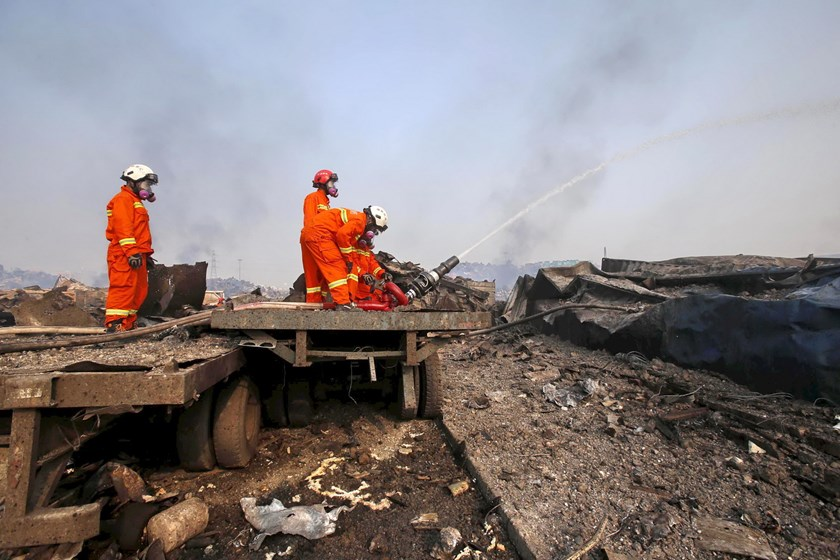 Firefighters wearing gas masks try to put out a fire at the site of Wednesday night's explosions in Binhai new district of Tianjin, China, August 15, 2015. Photo: Reuters/China Daily