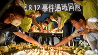 Residents and volunteers light candles as they attend a candlelight vigil to mourn the victims of Wednesday night's explosions, outside a hospital at Binhai new district in Tianjin, China, August 15, 2015. Photo: Reuters/Stringer