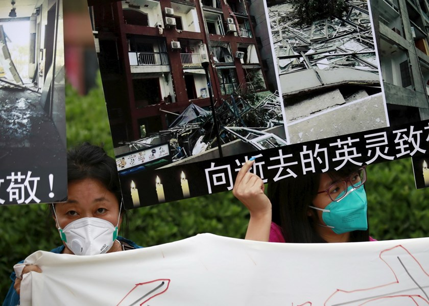 "Residents evacuated from their homes after last week's explosions at Binhai new district, hold placards bearing images of their damaged houses, at a rally demanding government compensation outside the venue of the government officials' news conference in Tianjin, China, August 18, 2015. The slogans on the placards read ""salute to the spirit of martyrs who passed away"". Photo: Reuters/Kim Kyung-Hoon"