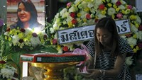 A relative of Thai victim from Monday's bomb blast, Waraporn Changtam, places a flower near her picture while praying during a Buddhist funeral at a temple in Nonthaburi province, on the outskirts o Bangkok, Thailand, August 19, 2015. Photo: Reuters/Chaiwat Subprasom