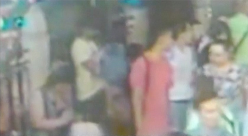 Still image from closed-circuit television (CCTV) footage released by Thai police shows what they believe to be two new suspects - dressed in red (C) and dressed in white (3rd R) - standing in front of previously identified suspect in yellow t-shirt removing his backpack prior to a bomb blast in Bangkok, made available August 19, 2015. Photo: Reuters/Thai Police