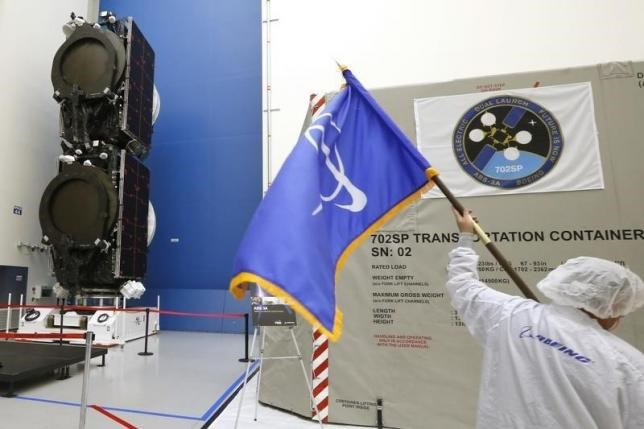 A man carries a flag with the Boeing logo past the world's first two all-electric propulsion 702SP satellites in the Boeing Satellite Development Center in El Segundo, California, January 9, 2015. Photo: Reuters/Lucy Nicholson