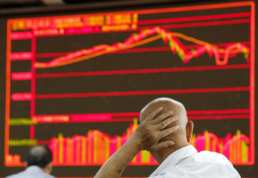 An investor looks at an electronic board showing stock information at a brokerage house in Beijing, China, August 25, 2015. Photo: Reuters/Kim Kyung-Hoon