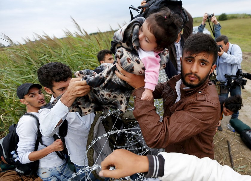 A Syrian migrant hands a girl to another migrant over the Hungarian-Serbian border fence, as they cross into Hungary near Roszke, August 26, 2015. Hungary's government has started to construct a 175-km-long (110-mile-long) fence on its border with Serbia in order to halt a massive flow of migrants who enter the EU via Hungary and head to western Europe. Photo: Reuters/Laszlo Balogh