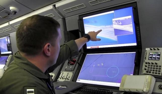 A U.S. Navy crewman aboard a P-8A Poseidon surveillance aircraft views a computer screen purportedly showing Chinese construction on the reclaimed land of Fiery Cross Reef in the disputed Spratly Islands in the South China Sea. Photo: Reuters/U.S. Navy/Handout via Reuters