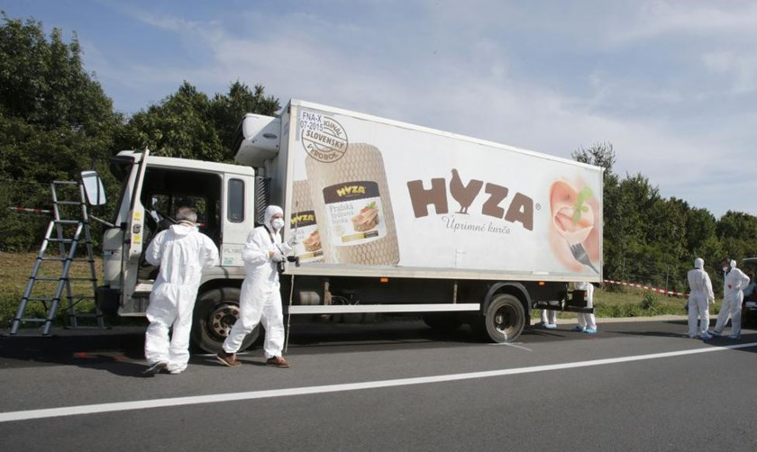 Forensic police officers inspect a parked truck in which up to 50 migrants were found dead, on a motorway near Parndorf, Austria August 27, 2015. Photo: Reuters/Heinz-Peter Bader