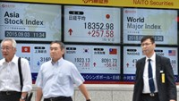 Pedestrians walk past a share price board of the Tokyo Stock Exchange (C, top) in Tokyo on September 3, 2015. Tokyo shares gained 1.42 percent September 3 morning after Wall Street rebounded overnight while Chinese markets are closed for a long weekend. Photo: AFP/Kazuhiro Nogi
