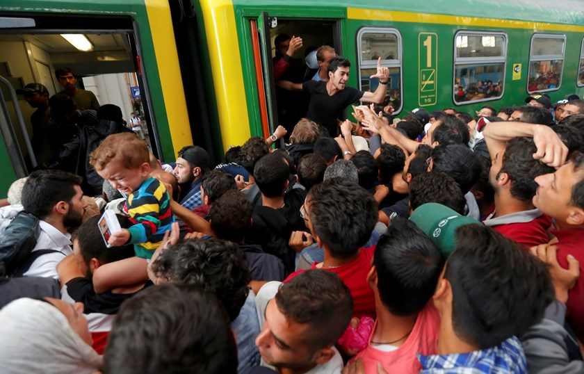 Migrants storm into a train at the Keleti train station in Budapest, Hungary, September 3, 2015 as Hungarian police withdrew from the gates after two days of blocking their entry. Photo: Reuters/Laszlo Balogh