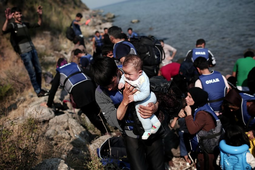 A refugee carries his child as they arrive on the shores of the Greek island Lesbos in an inflatable dingy across the Aegean Sea from Turkey on September 3, 2015. Photo: AFP/Angelos Tzortzinis